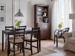 A Dining Room With Black Brown Table And Chairs Beige Seat Covers