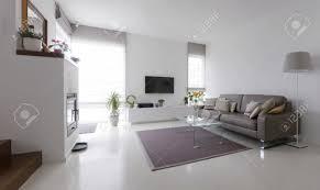 weiß wohnzimmer mit taupe ledersofa und glastisch