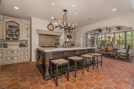 Spanish Style Kitchen With Off White Base Cabinets Dark Island Terra Cotta Floors