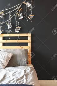 schwarze wand im gemütlichen schlafzimmer mit holzbett und lichterkette