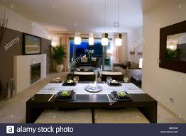 Openplan Dining And Livingroom In Modern Spanish Apartment With Fireplace Pendant Lighting