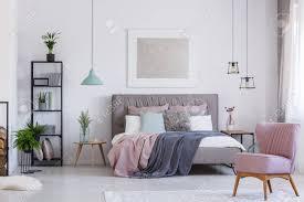 retro rosa stuhl in adorable rosa schlafzimmer mit pastell bettwäsche auf dem bett und blumen in glas farbe vase auf dem tisch
