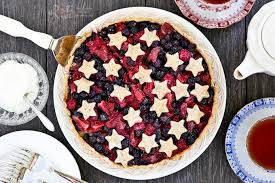 Delicious Triple Berry Tart with flaky hazelnut crust and juicy blueberries strawberries and raspberries