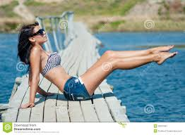 young beautiful on the pier at the river in denim shorts