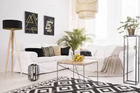 weißes modernes wohnzimmer mit schwarzen dekorationen und gemustertem teppich