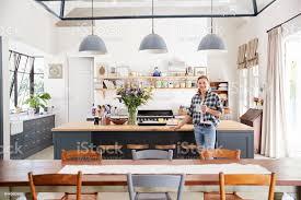 frau stützte sich auf insel in eine offene kücheesszimmer stockfoto und mehr bilder architektonisches detail