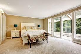 master schlafzimmer im amerikanischen stil doppelbett mit weißem kopfteil und bunten bank mit blumenmuster blick auf den balkon