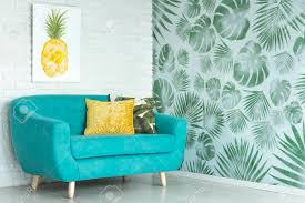 yellow pillow on blue sofa against a wall with pineapple poster