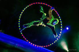 Acrobat with UV LED light Cyr Wheel in Black Light Show Anta Agni