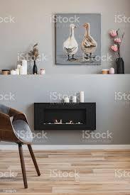 blumen in vasen kerzen und rustikale malerei im regal über ökokamin im modischen wohnzimmerinterieur stockfoto und mehr bilder aufgeräumter raum