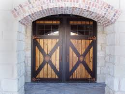 Double Cross Panel Entry Barn Doors With Curved Door Trim Using Brick Wall And Stone Material Rustic Facade House