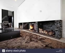 modernes wohnzimmer mit großem kamin mit schwarzen möbeln