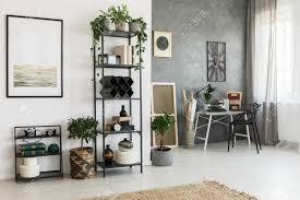 einfache malerei auf weißer wand im wohnzimmer mit dekorationen auf einem regal und pflanzen auf dem boden