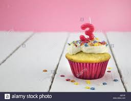 Happy birthday cup cake with star sprinkles and number 3 pink candle on white table with pink background Birthday celebration background for girl