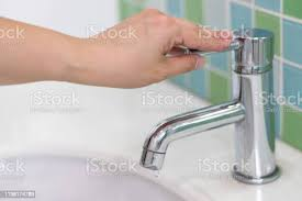 das bild des handschusses auf dem waschbecken im badezimmer wasser tropft um nicht mehr zu laufen da die den wasserhahn ausschaltet sparen sie