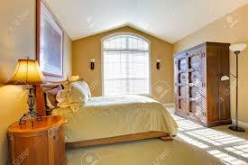 haupt schlafzimmer mit großem bett und alten schrank in warmen farben gelb