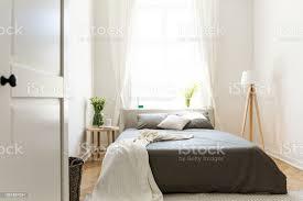 sonnigen natürlichen stil schlafzimmer mit einem bett in der mitte graue bettwäsche und kissen und vanille decke innenraum eine le und einen hocker