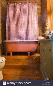 badezimmer mit stehender badewanne und rot weiss