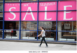 Woman Walking Past A Massive Summer Sale Sign At Multiyork Master Furniture Makers On Tottenham Court