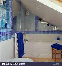 blue mosaic tiles in small attic bathroom with white tiled bath