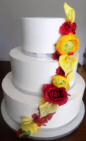 3 Tier Buttercream Wedding Cake Decorated With Silver Ribbons And An Assortment Of Red