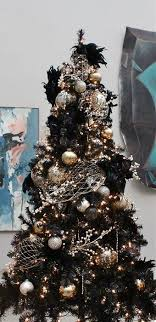 A Black Christmas Tree Decorated In Gold And Silver For Chic Gothic Inspired Look
