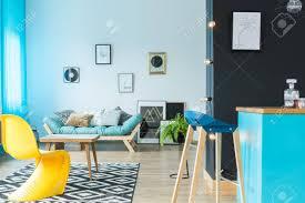 moderner designer barhocker in der blauen kücheninsel im farbenfrohen wohnzimmer mit gelbem stuhl