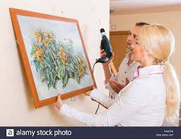 Positive Man And Woman Hanging Art Picture In Frame On The Wall Focus