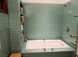 contemporary bathroom with drop in bathtub by subway tile