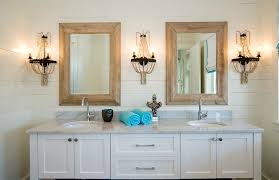 bathroom with wood framed mirrors and shell sconce lighting – at