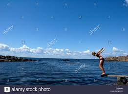 Side View Of A Girl About To Jump Into The Sea From Diving Board