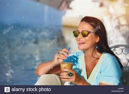 Happy Tanned Woman Drinking Iced Coffee In Seaside Cafe During Sunset Selective Focus Copy Space