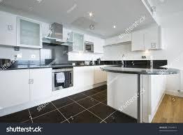 Modern White Kitchen With Granite Work Top Dark Tiled Floor And Appliances