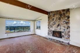 helle leeren wohnzimmer mit felsigen kamin gewölbte decke mit balken braun teppichboden und schönen blick gig harbor brücke durch das fenster