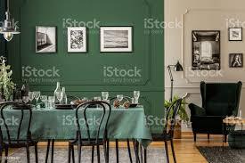 schwarzweiße plakate auf grüner wand stilvoller esszimmer mit holztisch mit weingläsern tellern und kegeln stockfoto und mehr bilder bilderrahmen