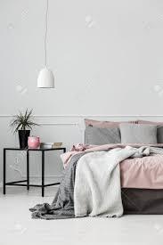 graue und rosa bettwäsche auf dem bett gegen weiße wand mit kopie raum im schlafzimmer interieur mit einer pflanze