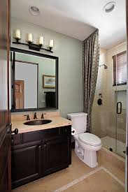 Lovely Black Single Sink Vanity Cabinet With White Toilet As Well Rustic 4 Light Wall Fixtures Small Tub Shower Room In Classy Guest Bathroom