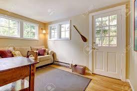 wohnzimmer mit sofa tür und schreibtisch in natürlichen farben mit parkettboden
