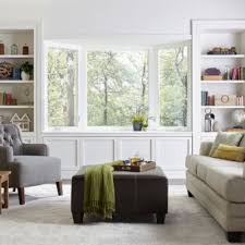 Bay Window In A Room With White Walls Bookshelves Gray Cushioned Chair And