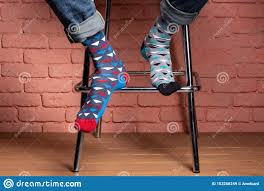 Legs Of A Man Sitting On A High Chair, In Socks Of Different ...