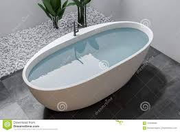 badewanne mit wasser im weißen badezimmer draufsicht stock