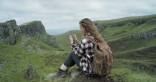 Independent Woman Traveller Sitting At Edge Of Cliff Looking Out