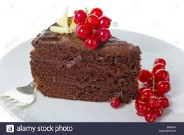 Slice of dark chocolate cake decorated with red fruit isolated on white Stock
