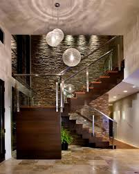 A Warm Wood Staircase Boasts Sleek Glass Railing And Stacked Stone Accent Wall While Brilliant Pendant Lights Glow Overhead