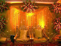 Indian Wedding Reception Decorations With Gold Padded Chairs And Red Carpet Also Large Curtains Plus White Flowers