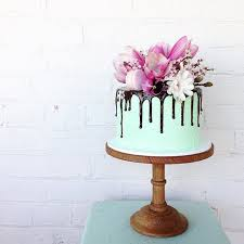 Chocolate Cake with green icing and chocolate drizzle topped with magnolias By Mudgee Made