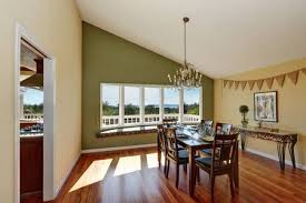 Elegant Dining Room With Contrast Olive Wall Vaulted Ceiling Comfortable Window Seat And Hardwood