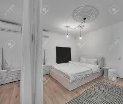 moderne schlafzimmer mit weißen wänden und ein parkett mit einem teppich auf dem boden es gibt ein bett mit weißen kissen und decke design