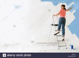 Smiling Woman On Ladder Painting Wall With Paint Roller