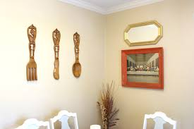 Wooden Utensils Last Supper And Gold Mirror Hanging In Dining Room